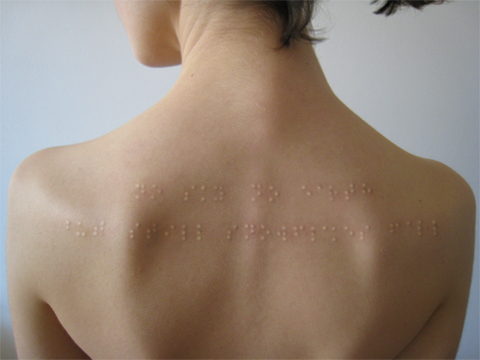 Klara Jirkova's Braille tattoo, a two-row pattern of tactile sentences across the upper back of a woman's body.