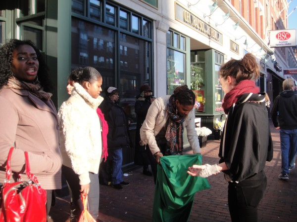 In Central Square, Cambridge, two women look on as a third tries on a green lycra body sock. I'm there, speaking with them about the project.