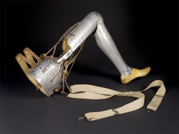"a ""hip disarticulation leg,"" from 1928. Metal limbs mimic the human form, with a colander-like bowl for the hip and canvas strap attachments"