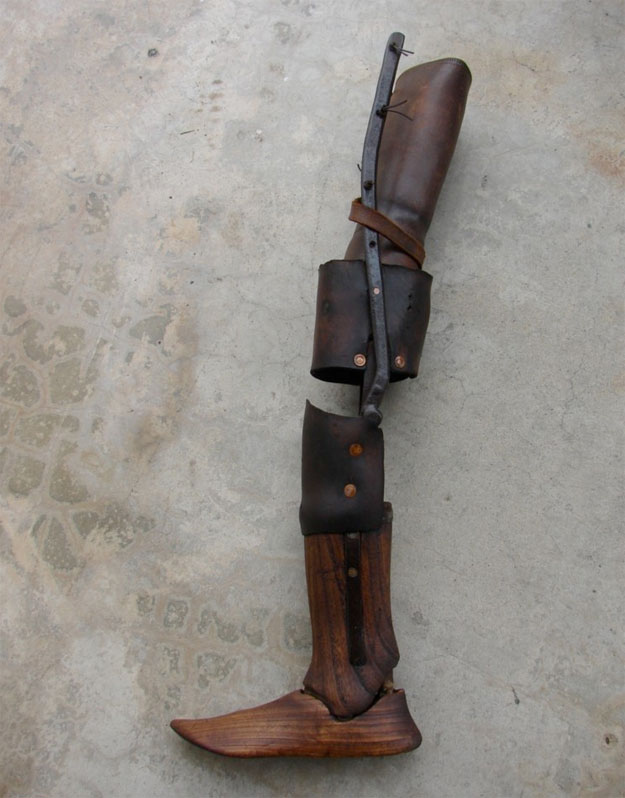 "A 19th century wooden leg, pieced together with leather parts at the knees and including a hinged ""ankle"""
