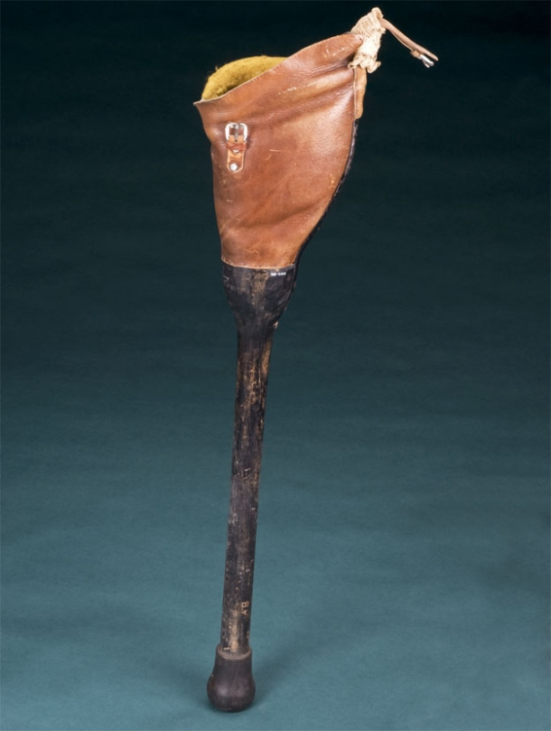 "a simple DIY artificial leg circa 1940. A wooden stick-leg adjoins the body with a ""leather knee-cap"""