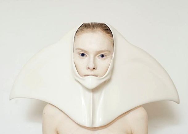 A woman's head is adorned with a sculptural covering resembling a fish's tail or a manta ray.