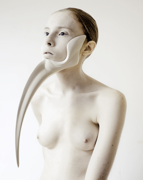 """A woman wears a piece of """"chin jewelry"""": a bone-white form that grasps her jaw and has a long horn-like protrusion from the chin."""