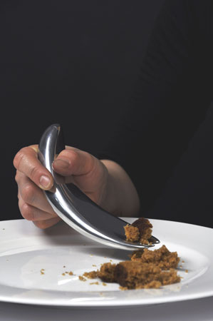 another close up of a proto-spoon in use, with a wider, curved structure all the way through, for easy scooping