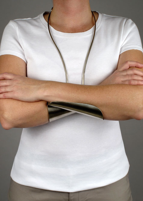 "A model wears a ""crossed arms"" necklace—wiring hangs from the neck, and two half-cupping splints support crossed overlapping arms."