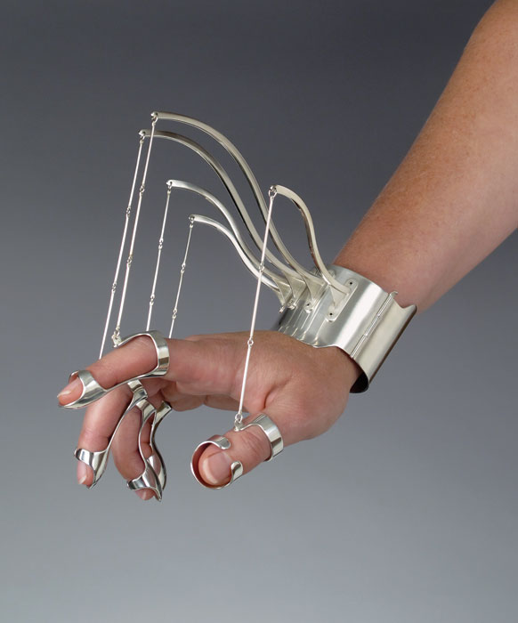 "A model wears an aluminum cuff bracelet, from which five metal ""marionette"" strings hang, with a ring for each finger. When the wearer's hand is braced by these rings and cuff, the just-so arranged hand evokes the poses of classical paintings."