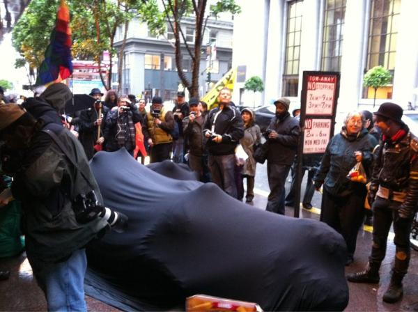 Several people share a single black body sock, seated on the street in San Francisco with an Occupy event. They resisted police arrest for 10 hours.