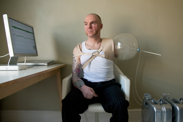 A man sits in a chair; he has one biological arm, and one arm fitted with a balloon-and-straw prosthetic, attached to CPUs. A computer monitor, close by, provides a read-out of data.