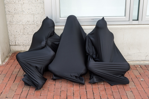 Three figures, seated outside, huddled together in separate black lycra body socks, enveloping their entire bodies.