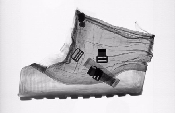 an x-rayed, transparent shot of a spacesuit boot, showing straps and buckles and the contoured curves where feet rest
