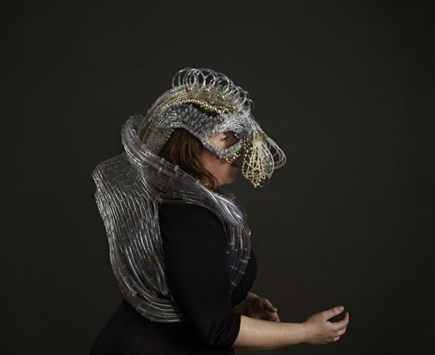 Side view of an opera singer, mid-song, while wearing the suit. This medium shot shows the tangle of tubing that wraps to the back of the head and loops around the shoulders and back—like a massive oxygen tank or backpack