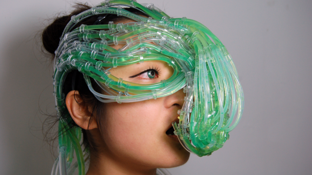 a close up of a woman wearing an elaborate, hydra-like head-and-face wearable of clear plastic tubing, looped and roped together at various intervals, and transporting green alga liquid to the mouth