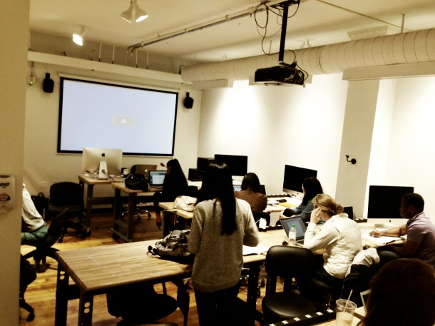 wide shot of my classroom at RISD: projector screen in front, rows of students at high desks with laptops