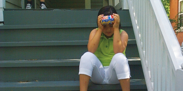 a young girl on a summer day, sitting on a stoop and holding a soda can horizontally, to cool her forehead.