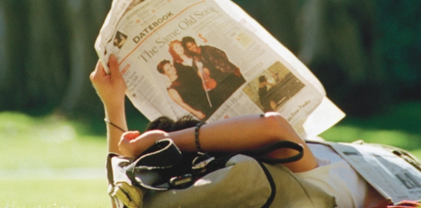 A man reclining outdoors uses his knapsack as a pillow, so he can read his newspaper with support.