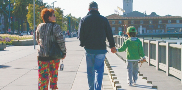 an adult man holds a small child's hand, walking side by side. the child walks on a raised wall or edifice, making their hands' height more equal.