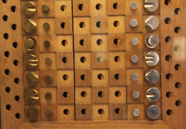 a wood and brass chess set, where squares have peg holes for each playing piece, and each brass unit has distinctive markings on top.