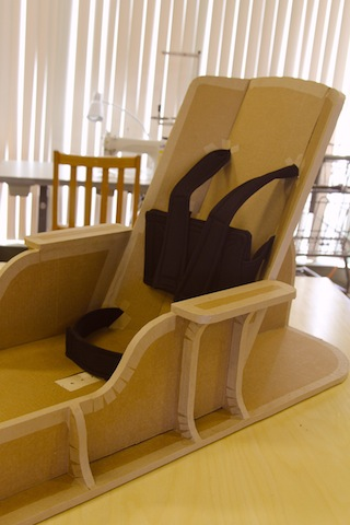 A floor sitter of cardboard with black neoprene straps for support, arm rests and a wide base.
