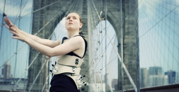 "Another medium shot of a woman ""playing"" the Brooklyn Bridge with her own stringed interface."