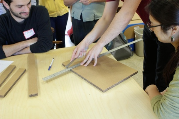 Students around a table while Molly scores a piece of cardboard with the blunt end of a fork.