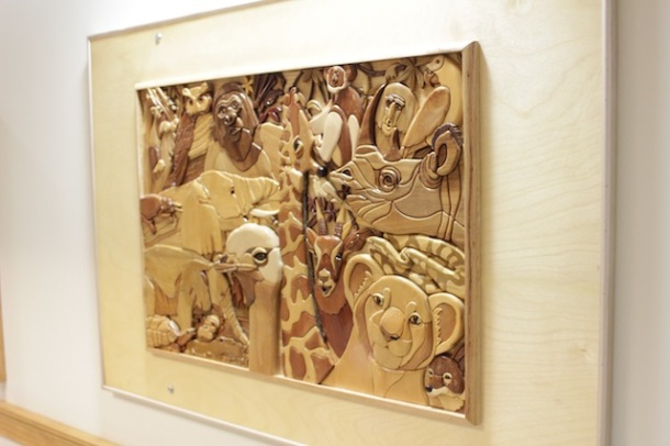 A wall hanging of multiple wood animal faces at various depths and in various wood stains. You can feel the heads of a tiger, a rhinoceros, a flamingo, giraffe, and many more.