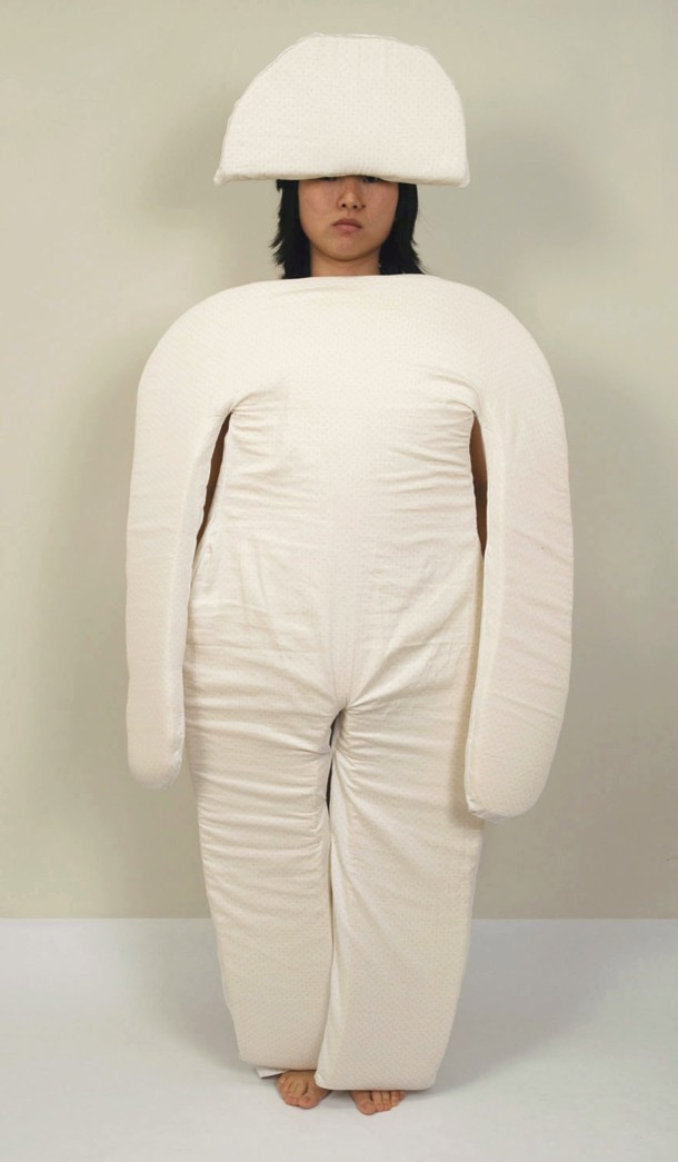 A woman wears the padding that would rest in the vertical bed: a series of cushions like an oversized set of pajamas, made to nest into the grooves and curves of the bed.