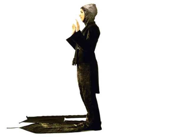 a woman wears an all-black suit, with blazer and coat, complete with unfolded prayer rug from the leg section of fabric, unzipped and spread on the floor, and a head scarf pulled from the back of the jacket.