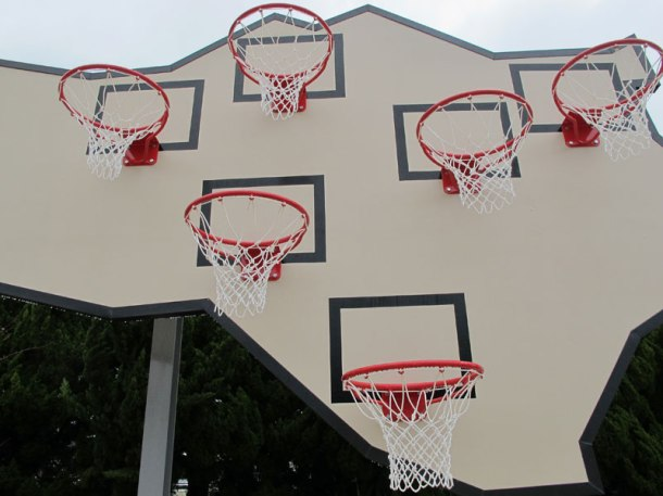 a large, angular, irregularly shaped backboard sits on two poles to make space for six basketball hoops, staggered at different heights