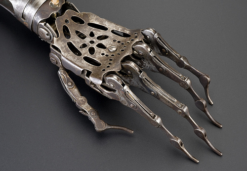 A Victorian-era prosthetic hand, made of delicate curving silver metal parts, fine hinges at the knuckles.