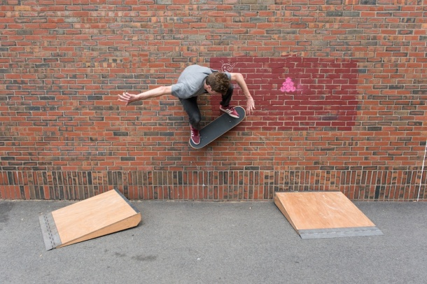 A skateboarder uses two of my ramp designs to skate across a wall in Boston.