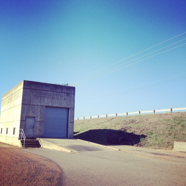 A public facilities building at Bona Dea Trail in Russellville, Arkansas: a simple concrete warehouse. The garage door is approached by a simple concrete ramp.