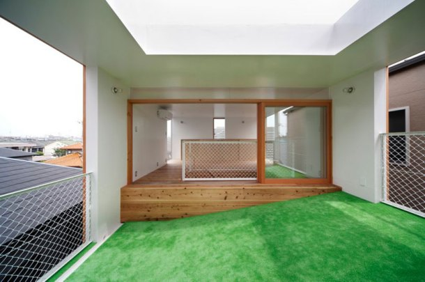 A house in Osaka, where an inclined plane covered in astroturf bridges indoor and outdoor space: windows to the outside on each end of the slope, and a skylight overhead. An invitation to lie on the grass, but with shelter.