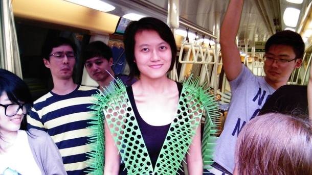 "Images: A woman wears a green mesh ""vest"" of perforated material, complete with spikes out the sides to ward off fellow commuters on a train. Sharp ends extend from shoulders and arms to indicate personal space. Renderings exhibit the scale and operation of the material."