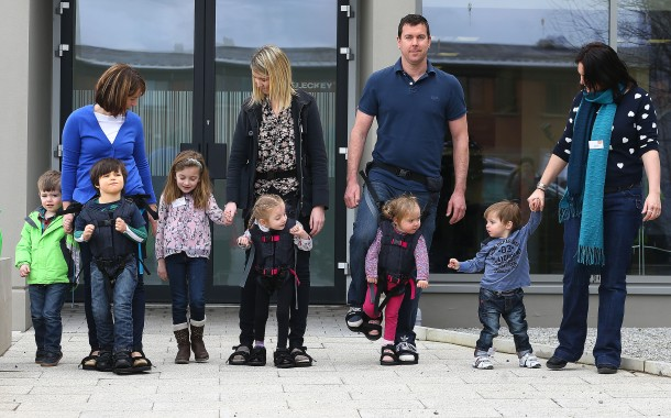 "Several adults ""wear"" their young toddlers in the Firely Upsee baby carriers, but inverted: the child is harnessed to an adult's legs and feet and strapped securely via the shoulders to the adult's waist, allowing simultaneous walking for both caregiver and young user."