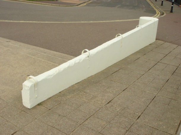 In England, a low concrete wall has its surface broken by looped metal rings placed every few feet, deterring skateboarders from its slope.