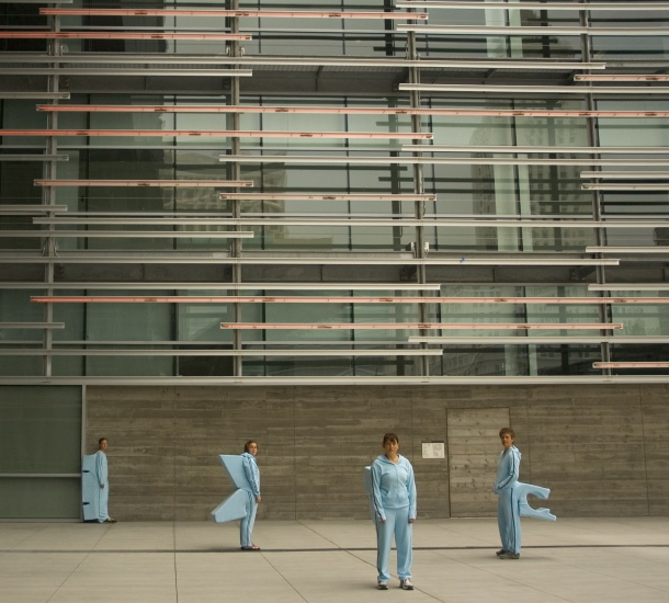 Four people wear pale blue, soft knit jogging suits, with soft geometric forms attached to their backs. Each form fits precisely over a designated architectural site, making it possible for a person to perch or sit at that site...