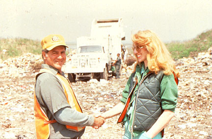 Mierle Ukeles shakes the hand of a New York City sanitation worker, against the backdrop of a landfill.