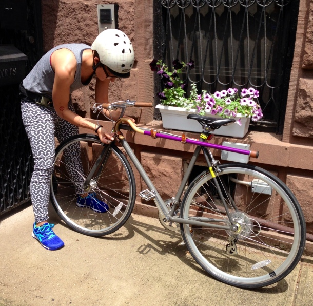 Liz Jackson on a New York City sidewalk, locking up her bike. Her purple cane is attached by leather straps and metal buckles in parallel to the bike's long body, keeping it secure and out of the way for her ride.