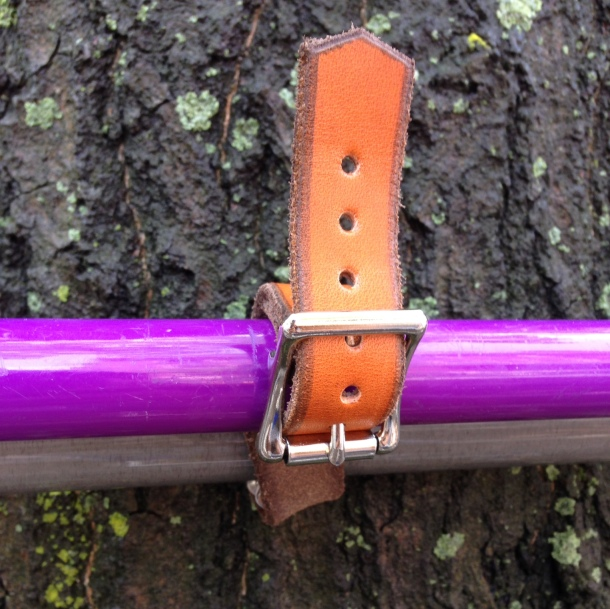 A close up of the honey-colored leather and metal buckle that attaches the purple cane to the bike.