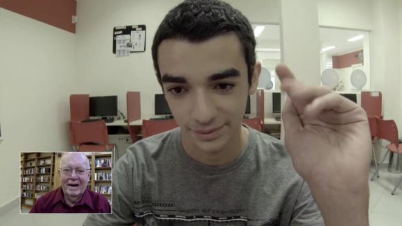 screenshot of a teenager using a skype-like application with his elder English-speaking partner in a thumbnail screen in the corner