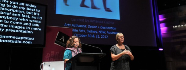 Amanda Cachia giving a lecture at a conference, at a traditional lectern.