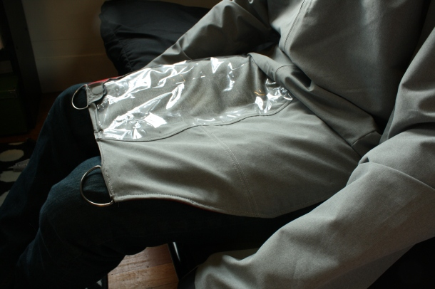The lap flap is unhinged from the front of the jacket and lies flat on a chair-user's lap, making belongings in an inside pouch accessible but secure.