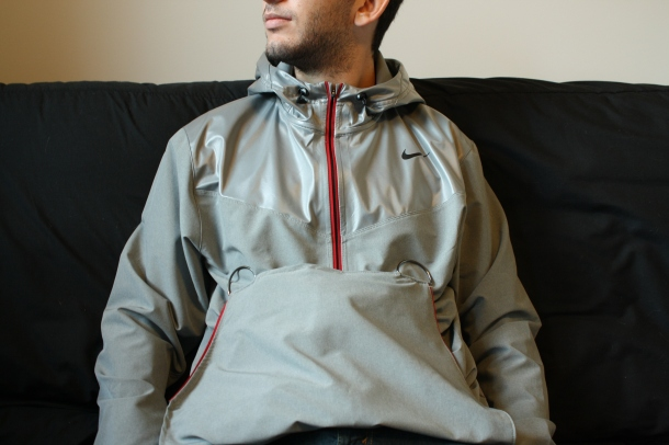 The RAYN jacket on a young man, seated. It's an altered Nike gray sports jacket with hoodie and zipper, but it's been radically customized in ways that are invisible at first glance.
