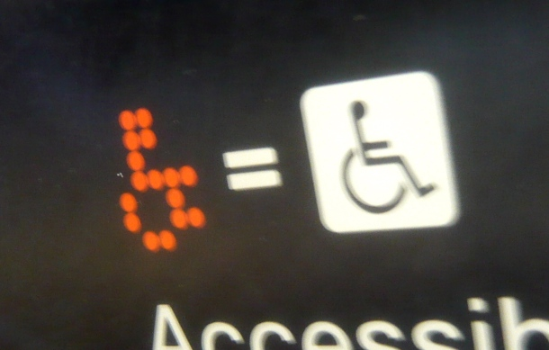 "Image: a digital dot matrix wheelchair on a screen, followed by an equal symbol, and the International Symbol of Access. Below it is a partially obscured printed ""accessible."" Credit: Jason Eppink on Flickr."